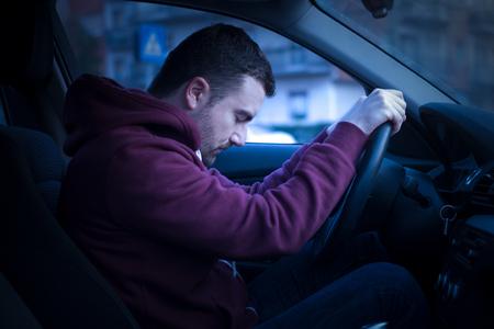 차를 운전하고 휠에서 잠드는 남자