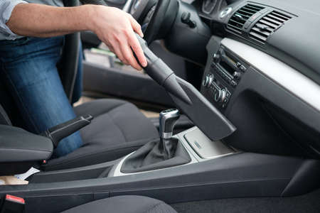appliance: Man vacuum cleaning his car seats interior