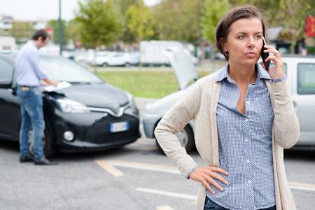 사고 후 자동차의 손상을 보험 담당자가 검토하는 동안 여성 운전자가 지시를 요구합니다.