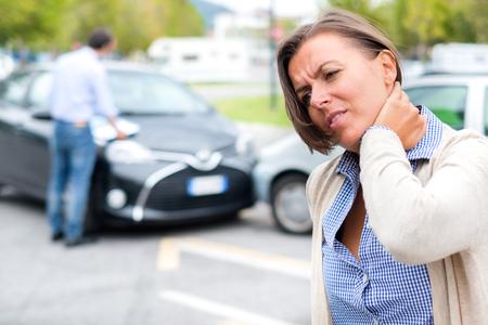 路上で車がクラッシュした後の女性の首を傷つける