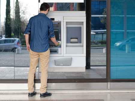 bankomat: Man using his credit card in an atm for cash withdrawal Stock Photo