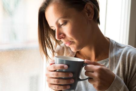 창 옆에 커피 초상화 한 잔 들고 슬픈 잠겨있는 여자
