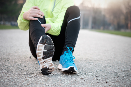 Runner with injured ankle while training in the city park in cold weather