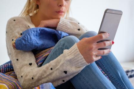 Meisje met telefoon zittend op het bed Stockfoto