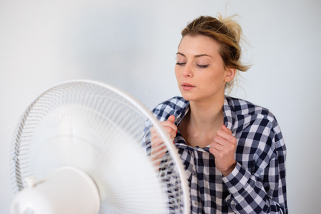 Girl face expression cooling in front of a fan Stok Fotoğraf - 88760547