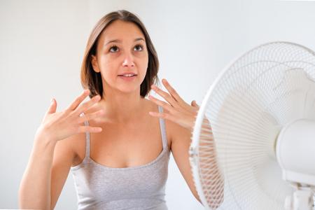 Vrouw het verfrissen zich voor een elektrische ventilatorventilator Stockfoto