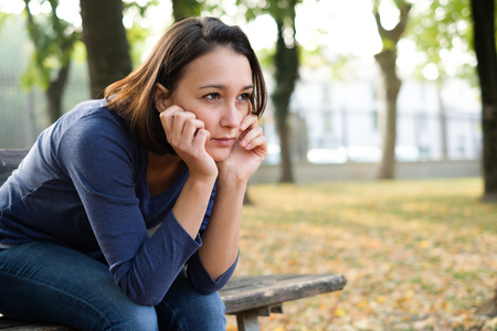 Sad girl sitting on a city park bench alone and thoughtful Stock Photo