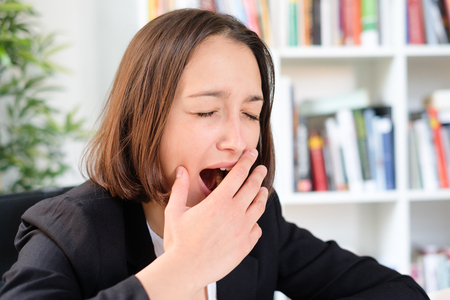 Tired employee yawning during work in the office