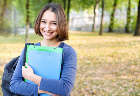 Happy and smiling student on public park background with copy space Stock Photo