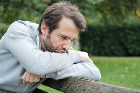 Sad and lonely man in troubles seated on a park bench