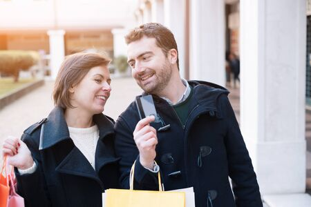 Man holding a credit card ready for the shopping time with his girlfriend