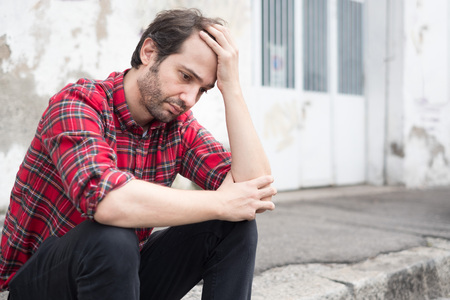 Sad man sitting alone in the street of the city Stock Photo