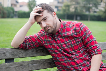 Sad and lonely man without a job seated on a park bench Stock Photo