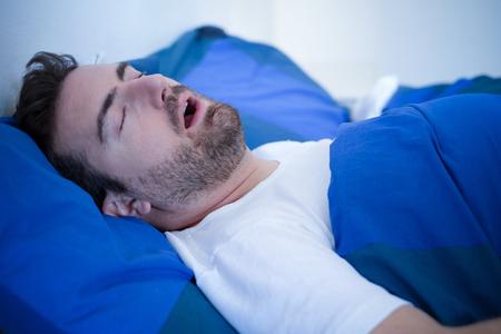 Mens in bed die voor het slaapapnoesyndroom lijden