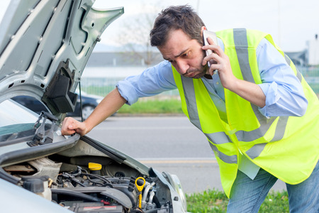 Upset man calling assistance mechanic service after car breakdown Stockfoto