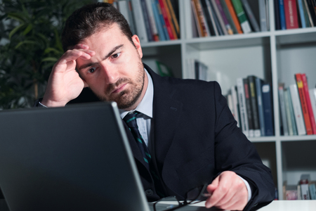 Tired and worried businessman working in the office at night Stock Photo