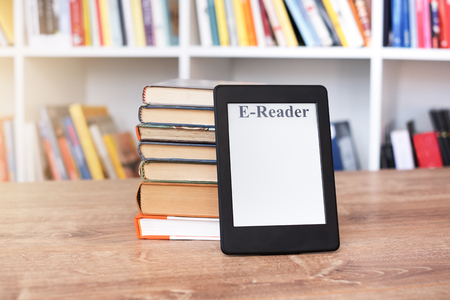 E-book reader and big pile of books