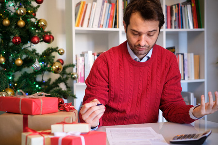 Man worried and with too many expenses for buying christmas present