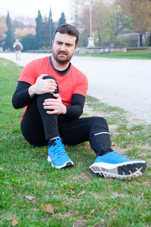 Male athlete suffering from pain in leg while exercising outdoors because overtraining