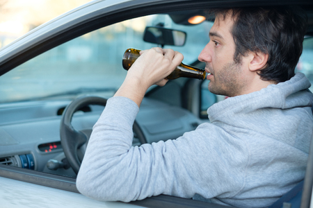 Dont drink and drive concept.Drunk man driving a car with a bottle of beer.