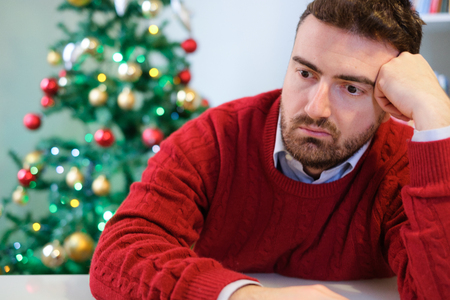 Sad man feeling negative emotions  and alone during christmas 스톡 콘텐츠