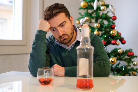 Sad man in solitude drinking alcohol all alone during christmas