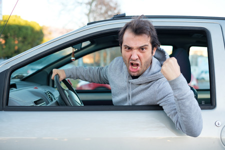 Portrait of angry driver at the wheel. Negative human emotions face expression Standard-Bild