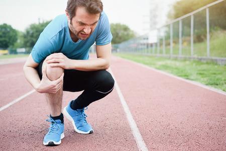 Running athlete feeling pain after having his knee injured Stock Photo