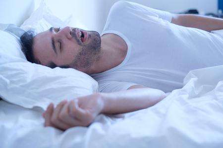 Schnarchen des Mannes wegen Schlafapnoe Sahs Syndrom, das im Bett liegt