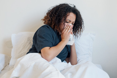 Sick and tired black woman lying in the bed Фото со стока