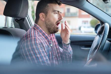 Verveeld en moe geeuwende man die in zijn auto rijdt, heeft rust nodig Stockfoto