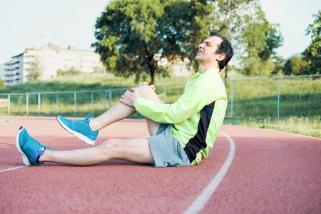 Running sportsman feeling pain after having his knee injured