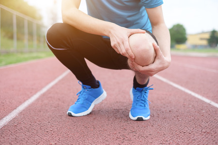 Running athlete feeling pain after having his knee injured Stock Photo