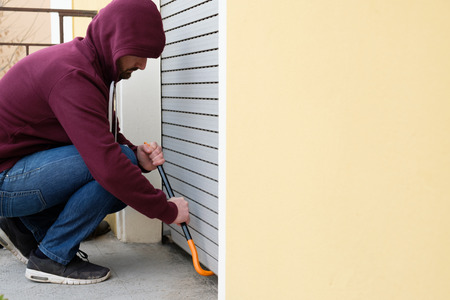 Hooded burglar forcing window shutter lock Stock Photo