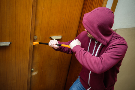 Hooded burglar forcing an home door lock