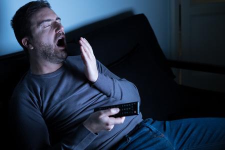 Portret van de mens die en op TV geeuwt kijkt
