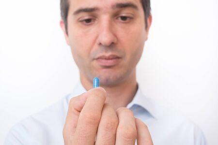 Ill man taking a blue medicine capsule Stock Photo