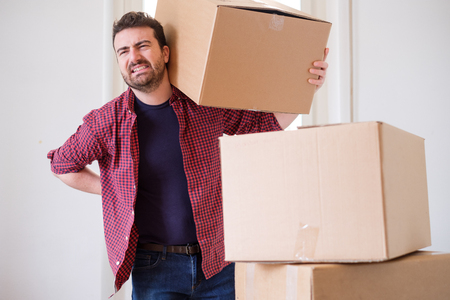 Man moving boxes and feeling back pain because heavy weight Stockfoto
