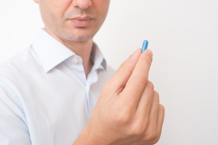 Head of sick man eating blue medicine pill