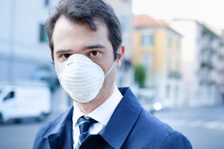 Man walking in the city wearing protection mask against smog air pollution Imagens