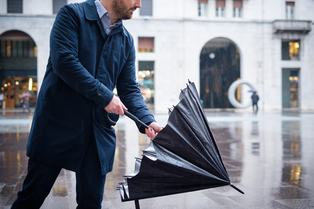 Man walking in the city with umbrella on rainy day