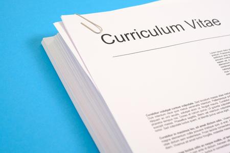 pila de cv y aplicación para el empleo en el escritorio azul