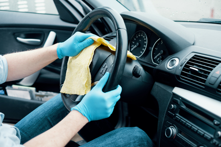 Man cleaning his car interiors and wheel