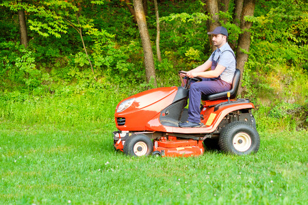 Gardener driving a riding lawn mower in a garden