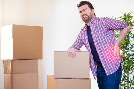 背中を感じる男痛いけいれん重い箱を動かす