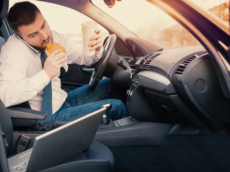 Man eating an hamburger and working seated in his car Archivio Fotografico - 99473234