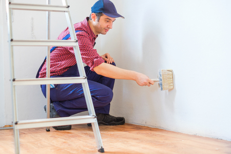 Bottom view of one painter man at work with a roller, bucket and ladder Standard-Bild - 115532383