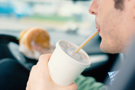 Man is dangerously eating junk food and cold drink while driving his car