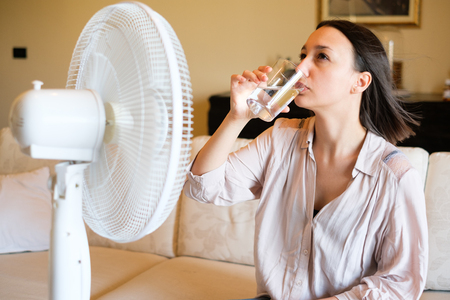 Woman feeling hot and trying to refresh in summertime heat