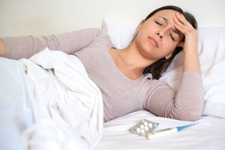 Woman feeling sick with thermometer and aspirin medicine pills in bed